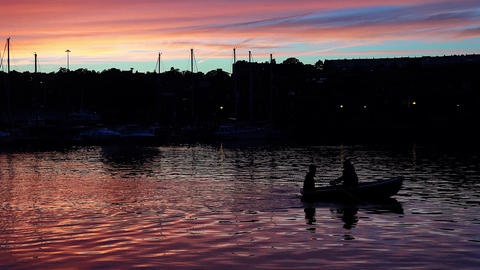 Two people in small row boat at sunset Footage