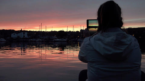 woman with iPad taking pictures of the river at the sunset Footage