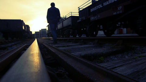 walking in the middle of the train tracks at sunset Footage