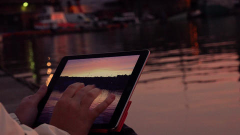 woman with tablet computer sitting on the dock of the harbor: watching photos Footage