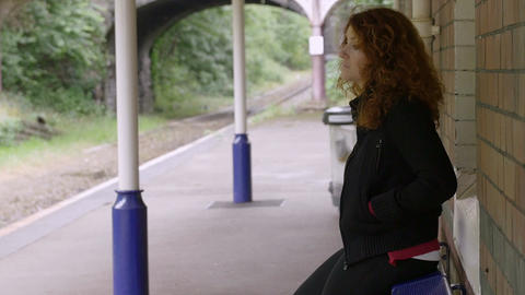 on the train station: countryside station with a sad woman waiting the train Live Action