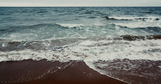 C4K wide angle graded shot of the ocean waves crashing a sandy beach Live Action