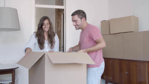 Caucasian man and woman unpacking cardboard boxes with stuff Live Action