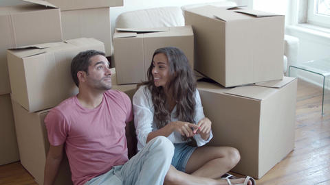 Young Caucasian couple sitting on floor near carton boxes Live Action