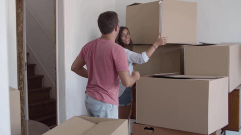 Beautiful long-haired lady giving cardboard boxes to man Live Action