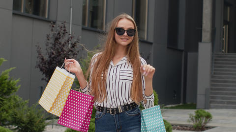 Stylish girl with shopping bags, rejoicing discounts in store, waving hands Live Action