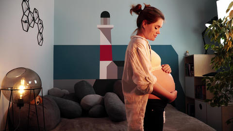 Young expectant mother in white shirt is stroking her belly staring ahead Live Action