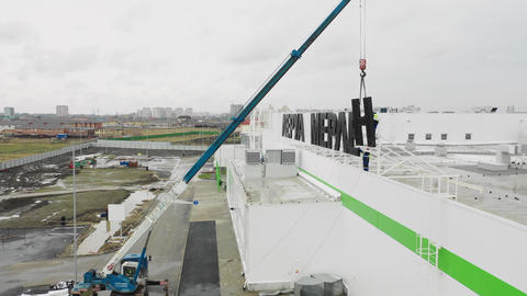 Installing letter of logo on supermarket facade with crane Live Action