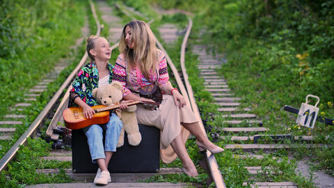 Happy traveling mom and daughter sitting on travel suitcase and singing song on Live Action