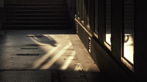 Shadowplay and reflections : passerbys walking through a passage (gangway) Live Action