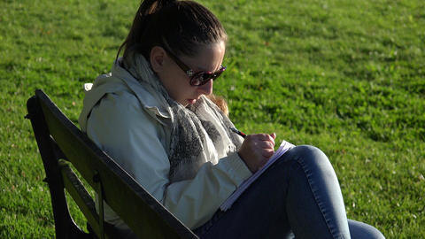 a girl writes her memories in a diary sitting on a park bench Footage