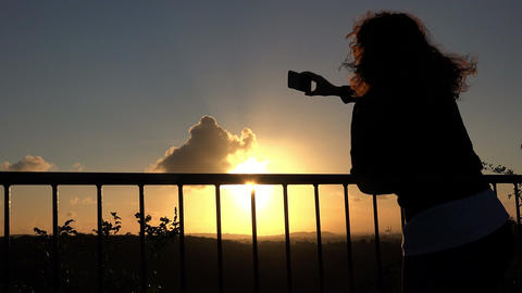 photographing the sunset: young woman climbing on the railing Footage