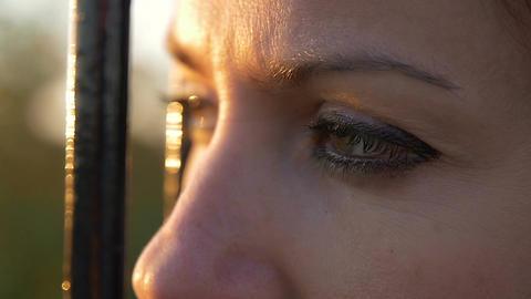 sad woman look: sad woman eyes behind an iron railing, sadness, loneliness Live Action