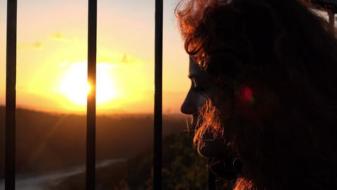 Woman searching of freedom behind the bars at sunset Footage