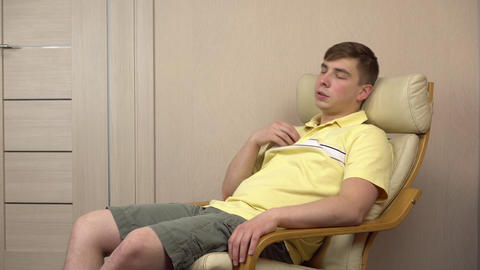 The young man is hot and he waves his hands. A man in a stuffy room sits on a Live Action