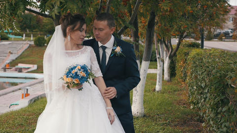 A beautiful newlywed couple hugs a rack among the beautiful green-red trees Live Action