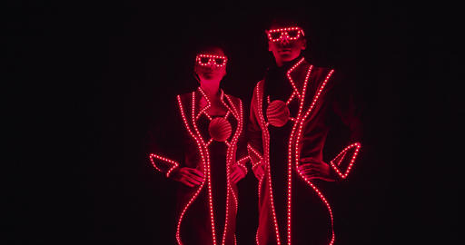 Performers in glowing costumes are standing in glowing red costumes, 4k Live Action