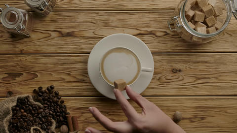 Neat woman's hand add brown sugar and stir with spoon into cappuccino coffee Live Action