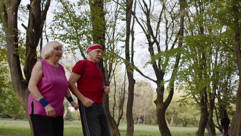 Sporty mature couple family jogging together. Senior husband and wife doing Live Action