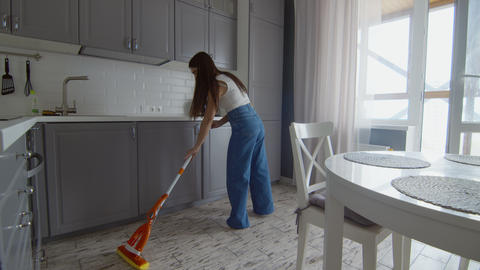 Young beautiful woman cleans floor with mop in kitchen Live Action