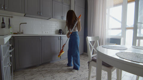 Happy and Cheerful young beautiful woman cleans floor and dances with mop like Live Action