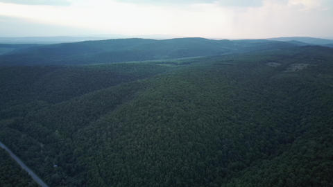 Aerial drone footage of mountains covered with green forest. Aerial video Live Action