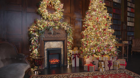 Beautiful room with decorated Christmas tree, gifts and fireplace on New Year Live Action