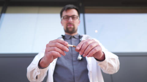 Stop smoking cigarettes concept. Doctor holding broken cigarette in hands Live Action