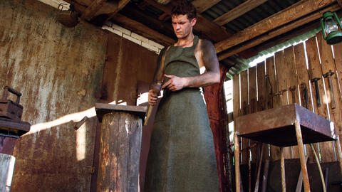 A Young Male Blacksmith Works In His Workshop.