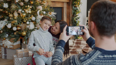 Mother and son posing for smartphone camera near Christmas tree while father Live Action