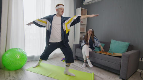 Retro stylish young woman eating pizza while her boyfriend doing yoga warrior Live Action