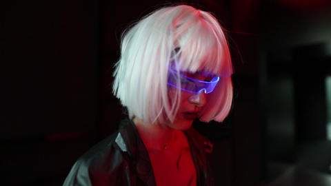 A woman in cyber glasses stands in the dark with neon lights Live Action