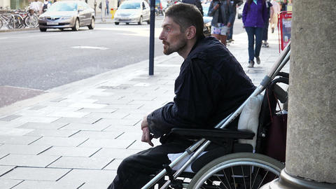 homeless bagging in the street: young disable on wheel chair Footage