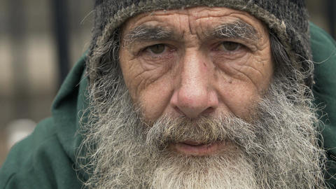 Homeless old man looking in the camera: poor man, beggar man, asking for charity Live Action