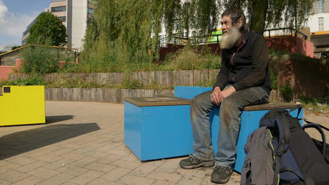 old homeless man sitting in a city square waiting for charity Footage