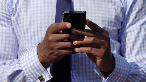 Businessman Near Office Building Sending Email With Cell Phone Footage