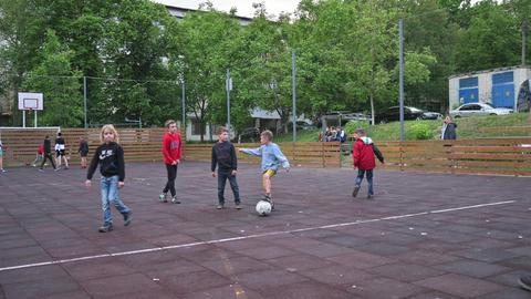 children of all ages playing football AKA soccer game in residential district ライブ動画