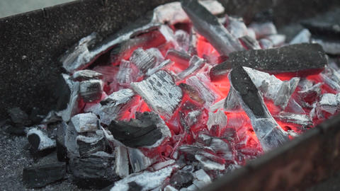 Hot coals on the grill. The coals are warmed to red in the grill Live Action