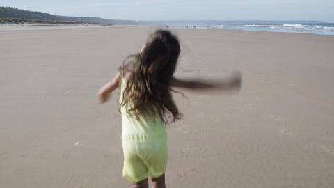 Little active black haired girl running on beach Live Action