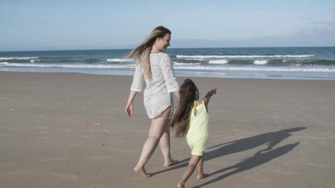 Happy mom and little daughter walking on beach to ocean Acción en vivo