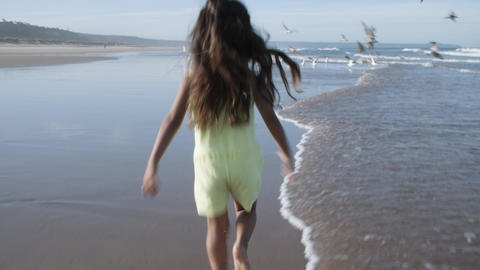 Active little black haired girl running on beach Acción en vivo