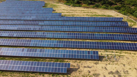 Solar panels on the field for power production. Solar power station, renewable energy, Aerial view Live Action