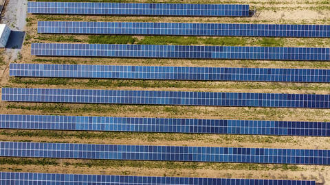 Aerial view of solar panels in a rows on field for producing energy. Renewable energy solar power Live Action
