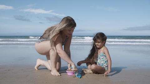 Cute little girl and her mom playing on beach Acción en vivo