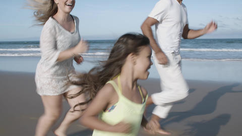 Happy family couple and little kid running on beach Acción en vivo