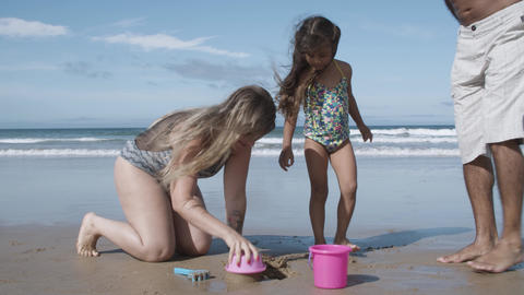 Parents helping cute little girl to build sandcastle Acción en vivo