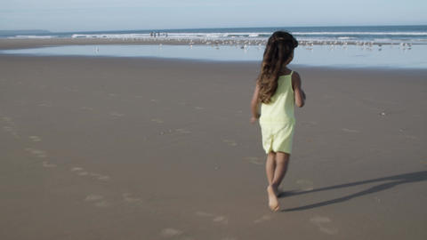 Joyful active little girl running on beach to water Acción en vivo