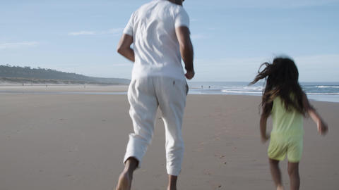 Back view of man and little girl running on beach to water Acción en vivo