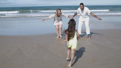 Little girl running on beach into her parents open arms Acción en vivo