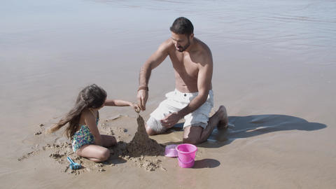 Cute little girl and her dad building sandcastle Acción en vivo